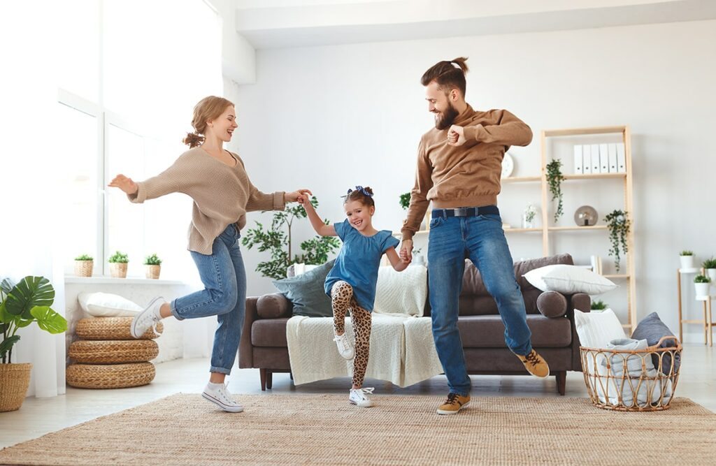 A mom and dad dance in their living room with their child.