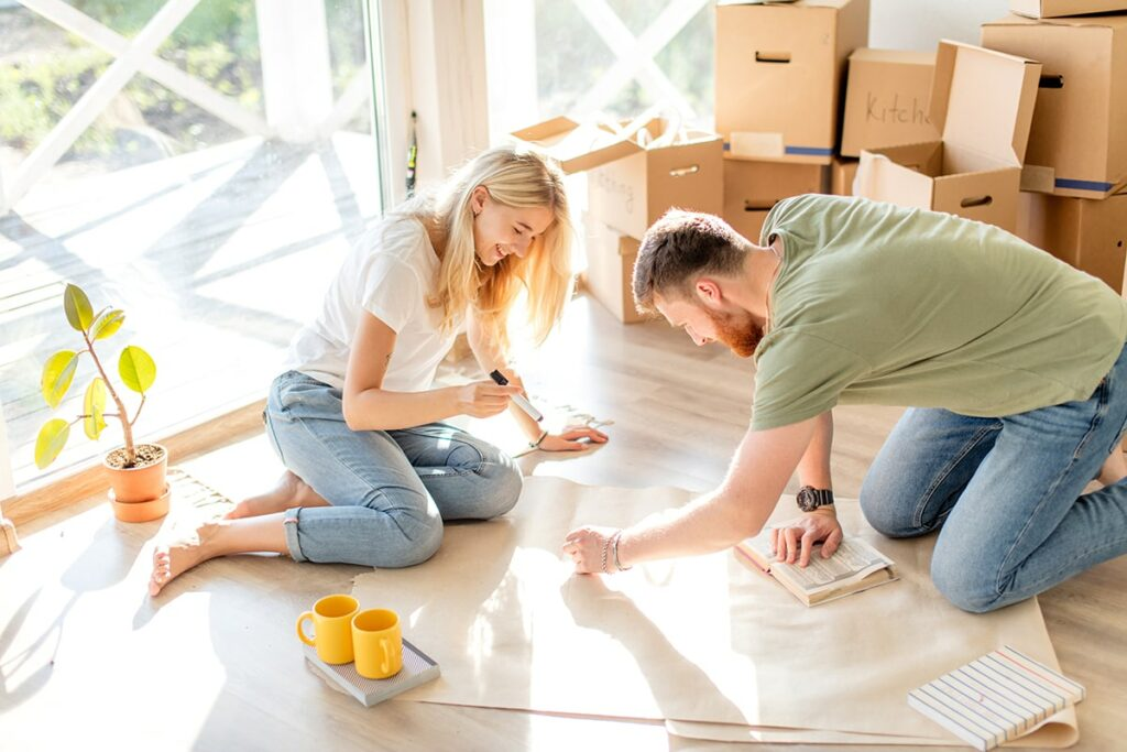 A young woman and man sit on a floor smiling while looking at the plans they're working on.